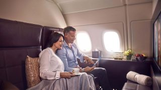 Eine Frau und ein Mann sitzen in der 1. Klasse eines Flugzeugs und schauen zusammen auf ein Tablet