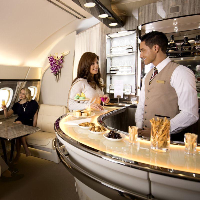 Eine Frau steht lächelnd an der Bar und interagiert mit dem Barkeeper, der zurücklächelt. Im Hintergrund sitzt eine lächelnde Frau, die ihr Glas erhoben hat.