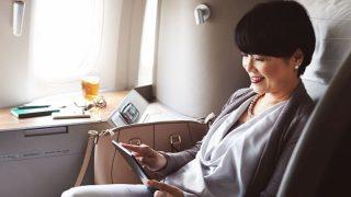 Eine asiatische Frau sitzt in einem Luxusstuhl und sieht auf ein Tablet.