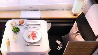 Auf einem quadratischen Tisch im Flugzeug steht ein Menü für einen Fluggast bereit.