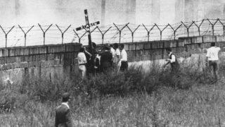 """13. August 1962: Am 1. Jahrestag der Mauer hielten mehrere West-Berliner ein Holzkreuz in die Höhe. Darauf zu lesen: """"Wir klagen an""""."""