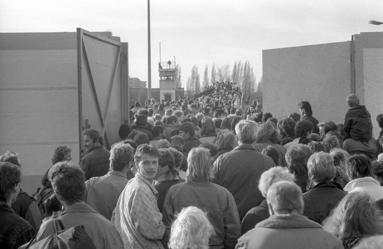 Kurz nach dem Mauerfall drängten Menschen aus Ost-Berlin durch ein großes geöffnetes Tor nach West-Berlin.