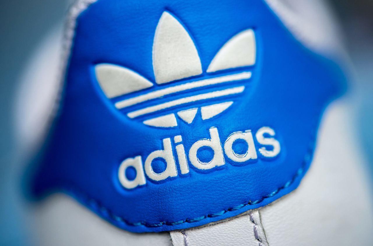 Weißes Adidas-Logo und Schriftzug auf einer blauen Schuhferse