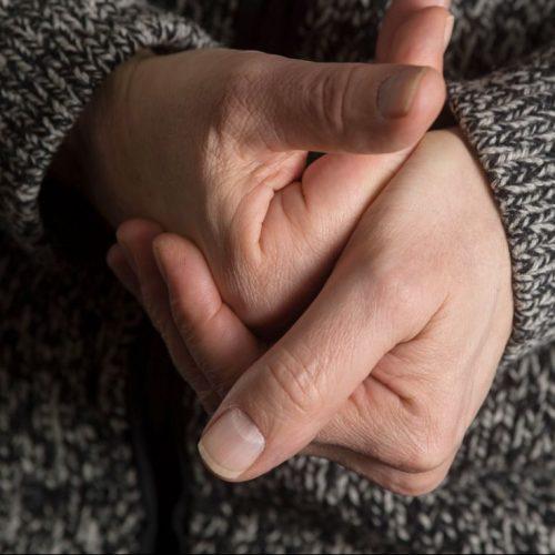 Zwei Hände vor einem grau melierten Pulli beim Fingerknacken.