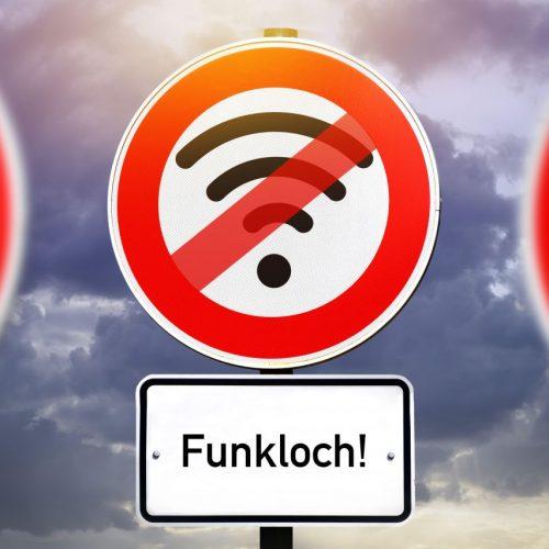 """Ein Straßenschild mit einem durchgestrichenen W-Lan-Symbol und dem Zusatzschild """"Funkloch""""."""