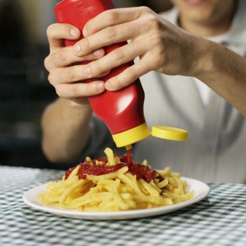 Junger Mann drückt Ketchup auf Pommes