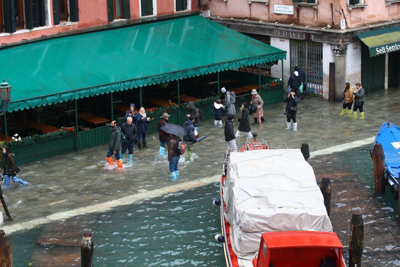 Touristen und Einheimische kämpften sich mit Gummistiefeln und wasserfester Kleidung durch die gefluteten Straßen.