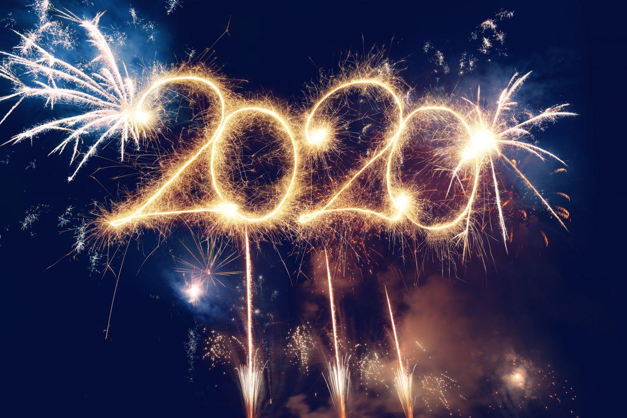 """Raketen und Feierwerk im Nachthimmel. Davor in Gold der Schriftzug """"2020""""."""