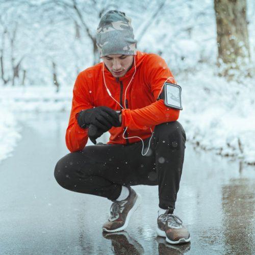 Man trägt Wearables während er Sport draußen macht
