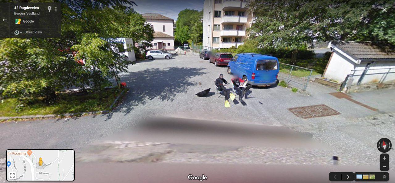 Zwei Männer in Taucheranzügen sitzen in einer Einfahrt auf Campingstühlen.
