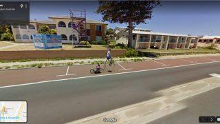 Ein Mann auf einem Fahrrad zieht im Anhänger ein Plüschkuscheltier hinter sich her.