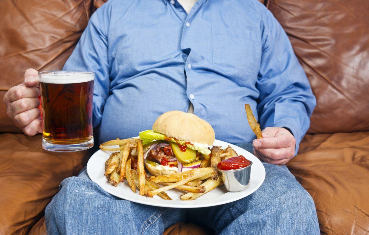 Mann isst Burger und Pommes