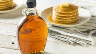 Ahornsirup wird zu Pancakes serviert