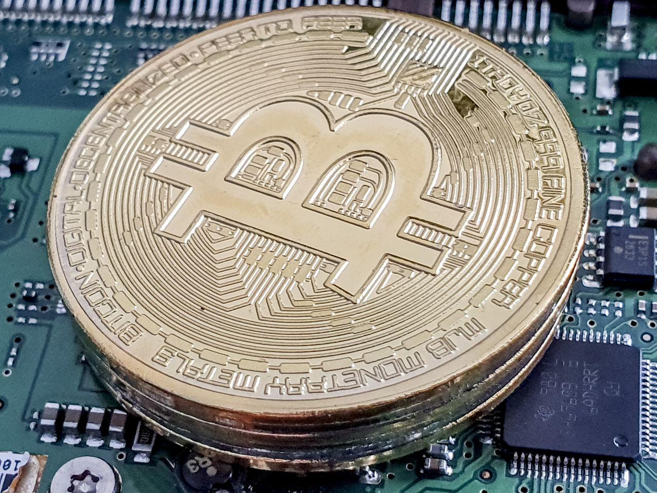 Eine Bitcoin-Münze liegt auf einer Rechner-Platine.