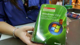 Eine Verkäuferin hält die Verpackung von Windows Vista in die Kamera.