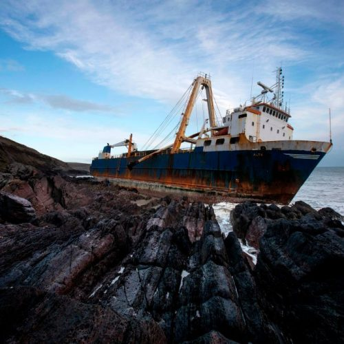 """TOPSHOT - The abandoned 77-metre (250-feet) cargo ship MV Alta is pictured stuck on rocks near the village of Ballycotton south-east of Cork in Southern Ireland on February 18, 2020. - A """"ghost ship"""" drifting without a crew for more than a year washed ashore on Ireland's south coast in high seas caused by Storm Dennis, the Republic's coast guard said. (Photo by Cathal Noonan / AFP) (Photo by CATHAL NOONAN/AFP via Getty Images)"""