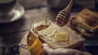 Honig wird auf Brot geschmiert
