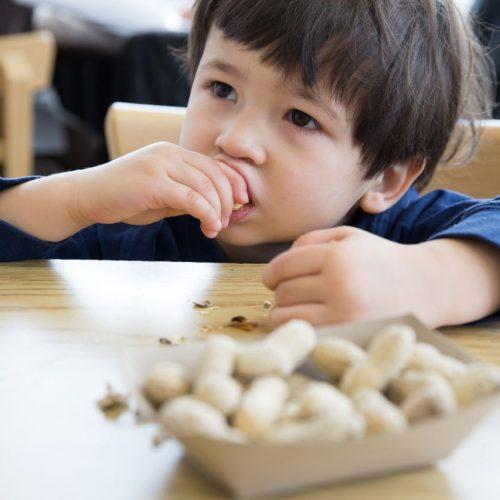 Junge isst Erdnüsse