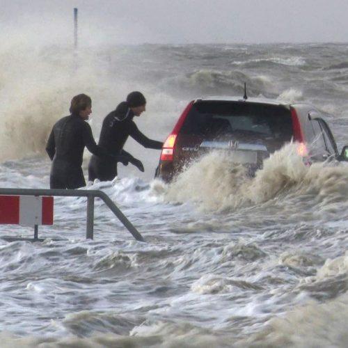 Ein Auto umtost von den Wellen einer Sturmflut.