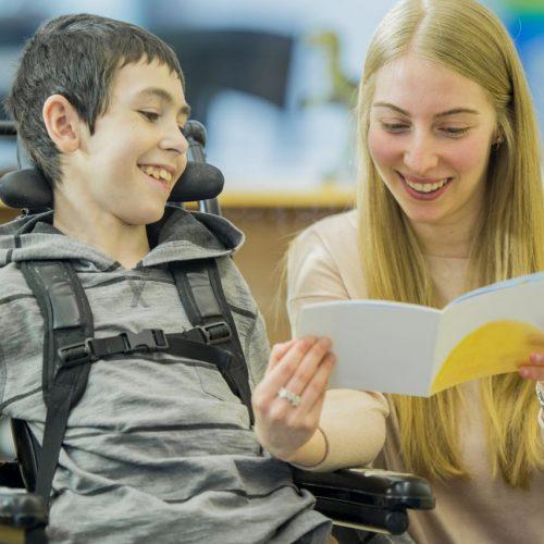 Junge Frau liest behindertem Junge vor