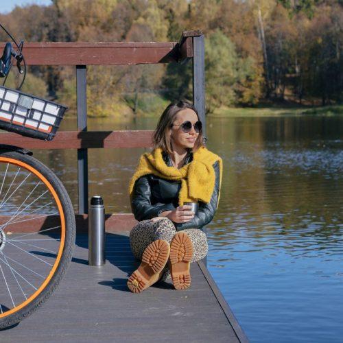Frau macht mit dem Fahrrad eine Pause am See