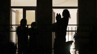 Eine klatschende Familie auf einem Kölner Balkon