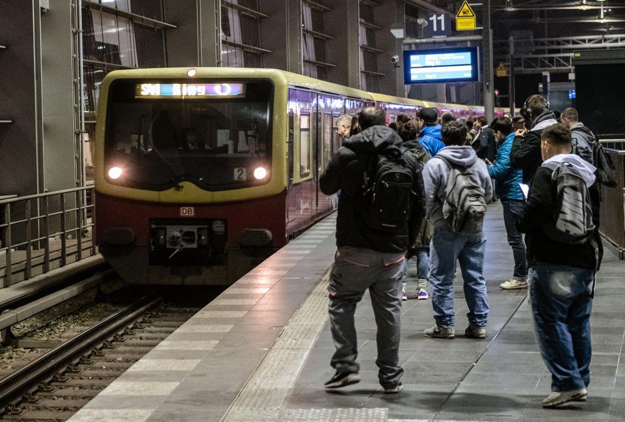 Pendler warten auf eine einfahrende S-Bahn.