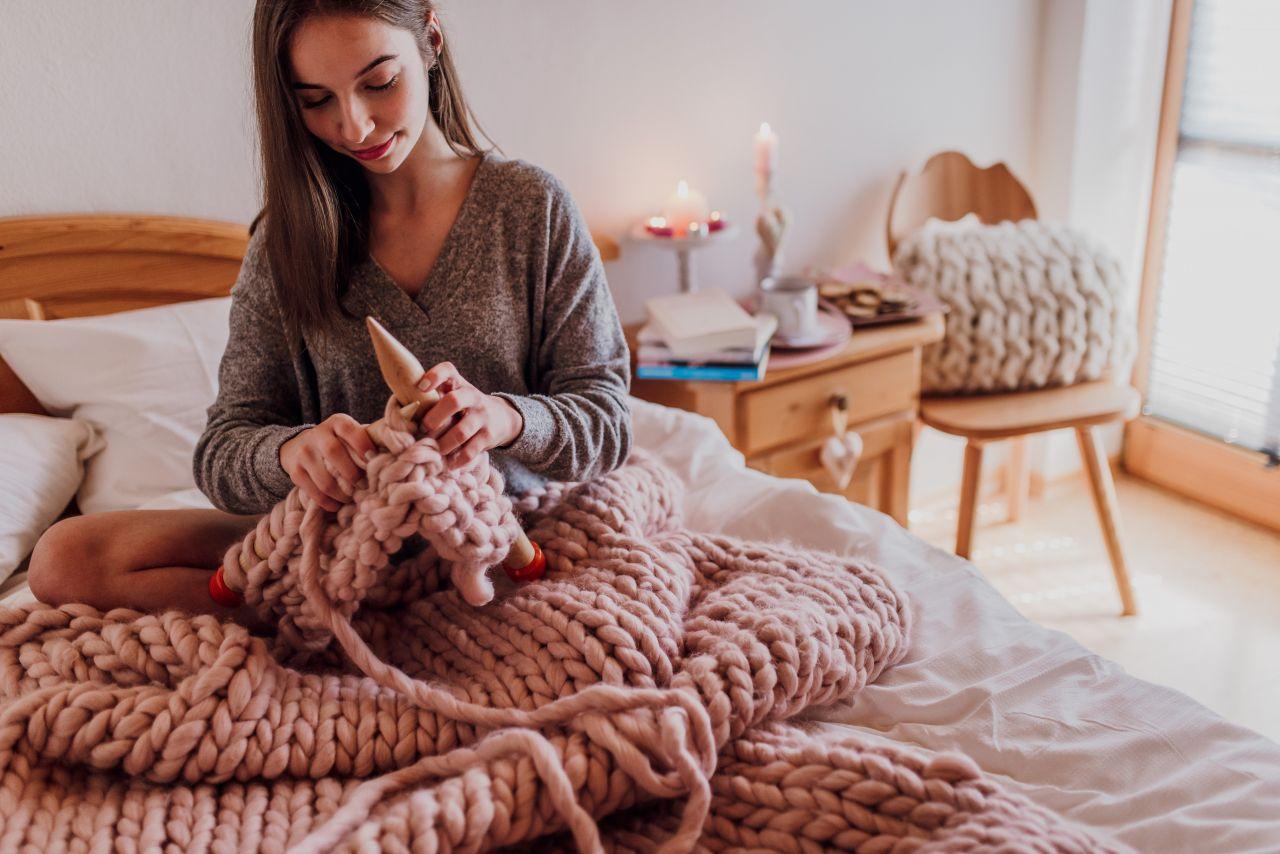 Junge Frau strickt im Bett