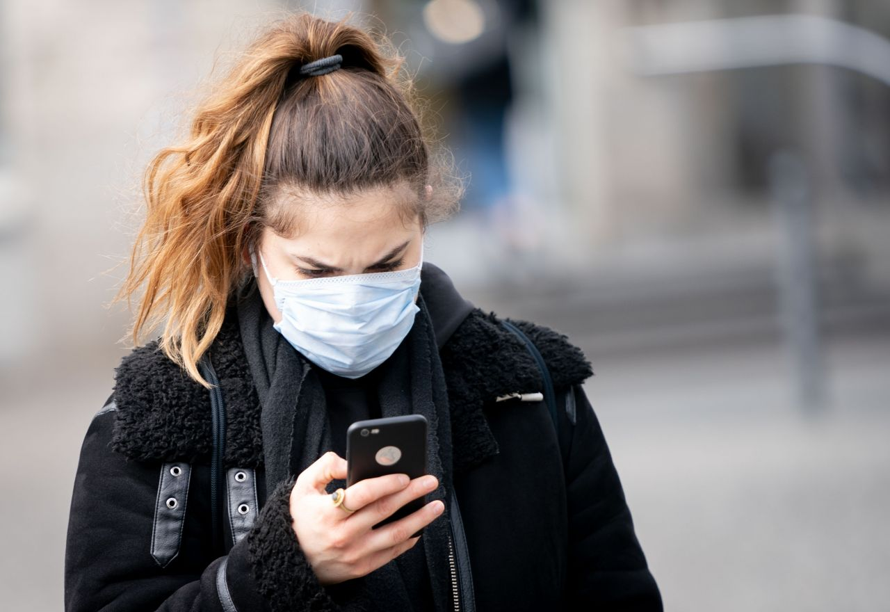 Eine Frau blickt auf dem Alexanderplatz auf ihr Smartphone. Die Bundesregierung setzt große Hoffnungen in eine App zur Nachverfolgung von Corona-Infektionsketten.
