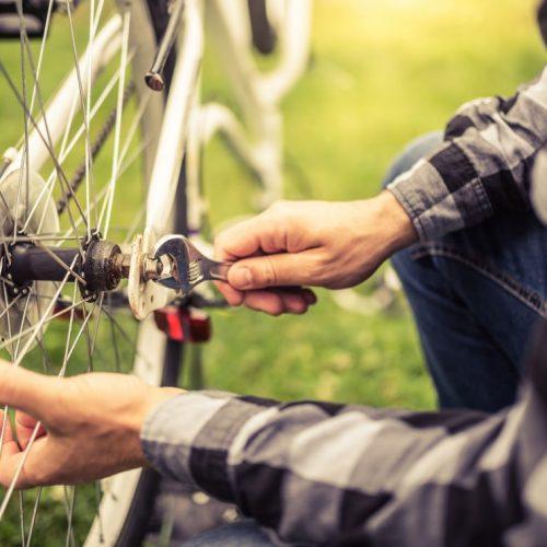 Mann repariert sein Fahrrad