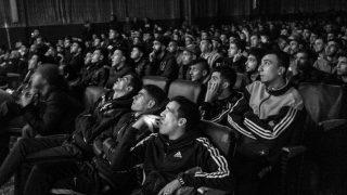 Jugendliche gucken in Algier in einem Kino Fußball.