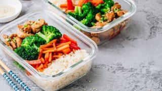 Behälter aus Glas mit Reis, Gemüse und Fleisch.
