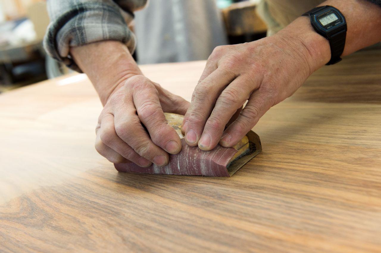 Eine Hand führt Schleifpapier über eine Holzplatte.