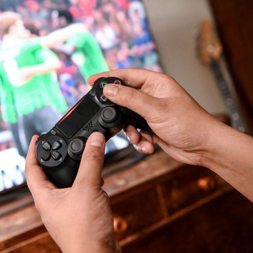 Ein Mann hält einen Controller, im Hintergrund läuft das Videospiel Fifa.