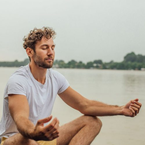 Mann meditiert am See.