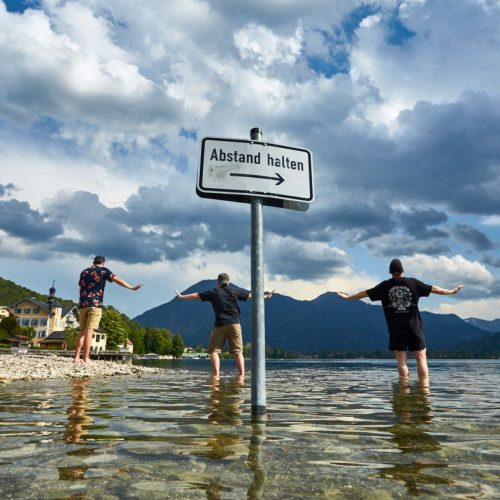 3 Männer halten Abstand in einem Badesee während der Corona-Pandemie
