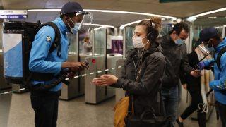 Frankreich, Paris: Mitarbeiter der Pariser Metro sprühen einem Pendler in einer Metrostation etwas hydroalkoholisches Gel auf die Hände. Nach zwei Monaten dürfen die Franzosen ihre Häuser und Wohnungen ohne Erlaubnisscheine verlassen.