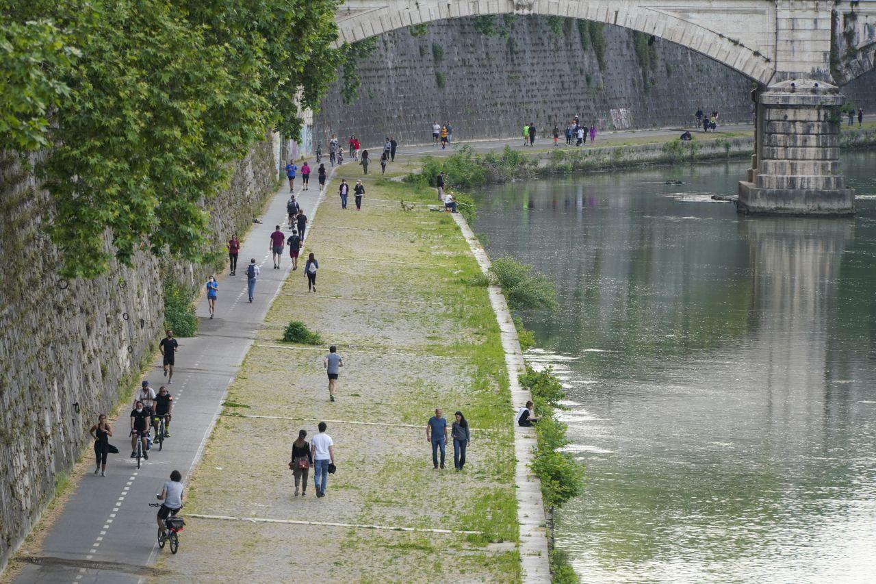 Italien, Rom: Die Maßnahmen zur Eindämmung der Corona-Pandemie werden langsam gelockert werden - Menschen spazieren am Fluss Tiber.