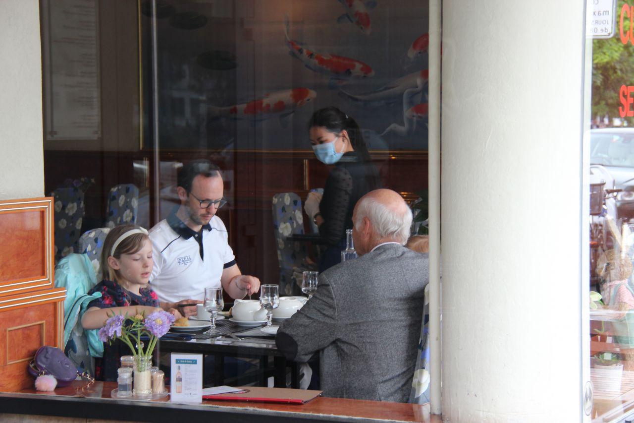 Schweiz, Genf: Menschen sitzen in einem Restaurant beieinander. Rund acht Wochen nach der Schließung treten in der Schweiz Lockerungen der Corona-Einschränkungen in Kraft.