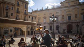 """Spanien, Tarragona: Ein Kellner mit Mundschutz trägt ein Tablett mit Biergläsern auf der Terrasse einer Kneipe, nachdem die Maßnahmen gegen die Ausbreitung des Coronavirus gelockert wurden. Zehn von insgesamt 17 """"autonomen Gemeinschaften"""" in Spanien durften in die """"Phase 1"""" des Deeskalationsplans vorrücken."""
