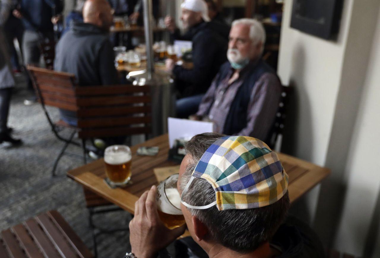 Tschechien, Prag: Ein Mann, der seinen Mundschutz auf dem Hinterkopf trägt, trinkt ein Bier in den Außenbereich eines Restaurants.