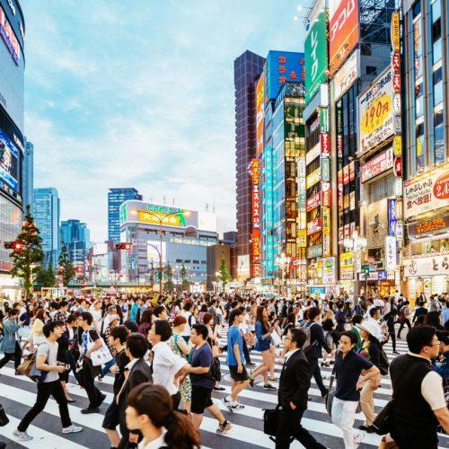 Menschen auf einer Hauptstraße in Tokio.