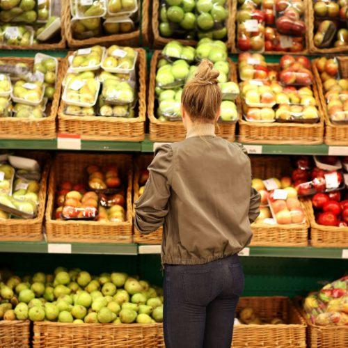 Frau steht vor Gemüse- und Obstregal.