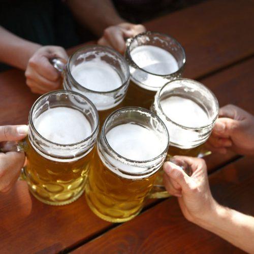 Freunde stoßen im Biergarten mit Bier an