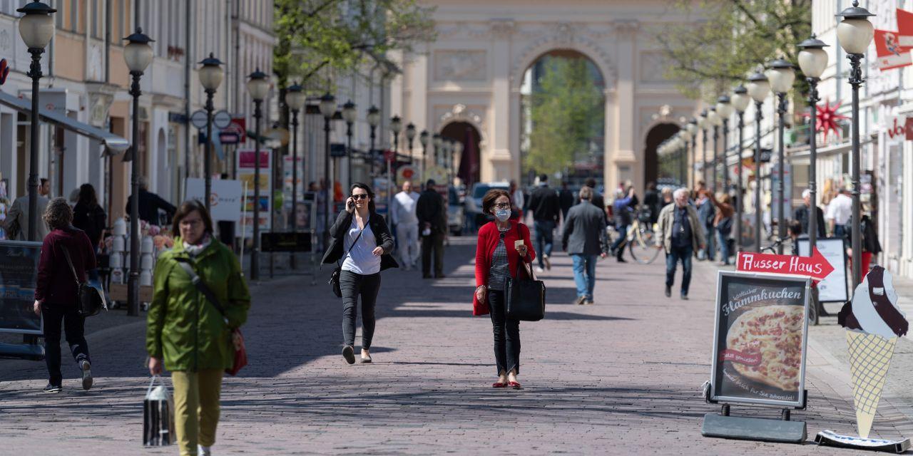 Eine Frau mit Mundschutz und Einkaufstasche geht aus Richtung Brandenburger Tor kommend auf der Einkaufsmeile Brandenburger Straße.