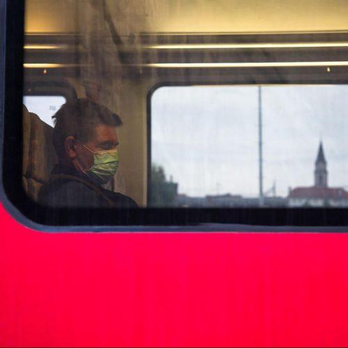 Mann fährt mit Maske Zug