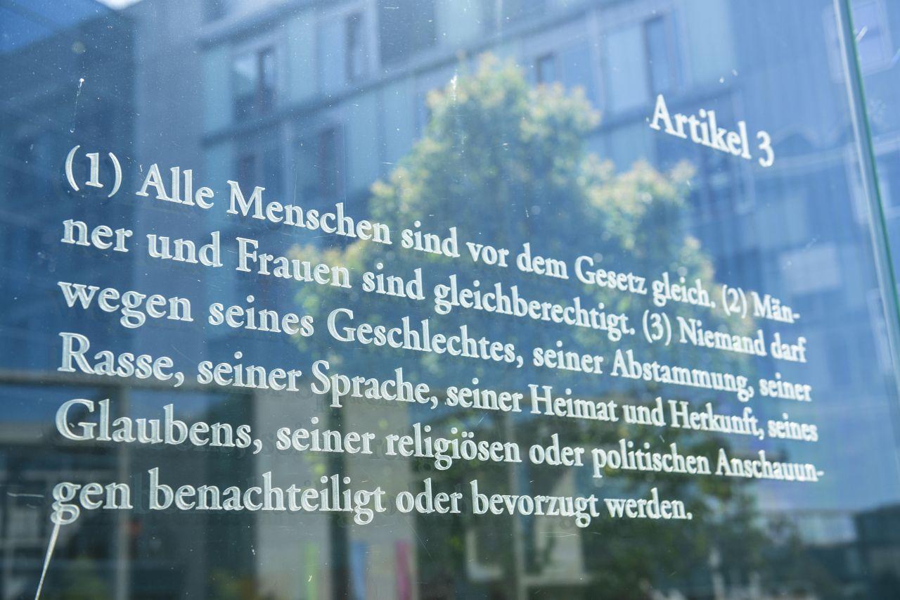 """Der Artikel 3 des Grundgesetzes steht auf einer Platte aus Glas in Berlin Mitte. An der Promenade der Spree verbinden 19 jeweils drei Meter hohe Glasscheiben einen Außenhof des Jakob-Kaiser-Hauses mit dem Uferbereich. Mit Laser sind in die Glasscheiben die 19 Grundrechtsartikel des deutschen Grundgesetzes eingegraviert. Die Installation ist ein """"Grundgesetz 49"""" benanntes Werk des israelischen Künstlers Dani Karava."""
