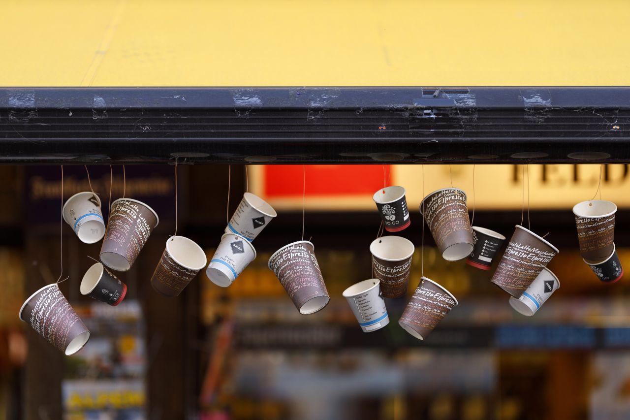 Take-Away-Regelungen statt Restaurantbesuch lassen während der Corona-Krise den Müll in Großstädten anwachsen, hier wiederverwertete Kaffeebecher als Girlande an einem Kiosk in Köln.