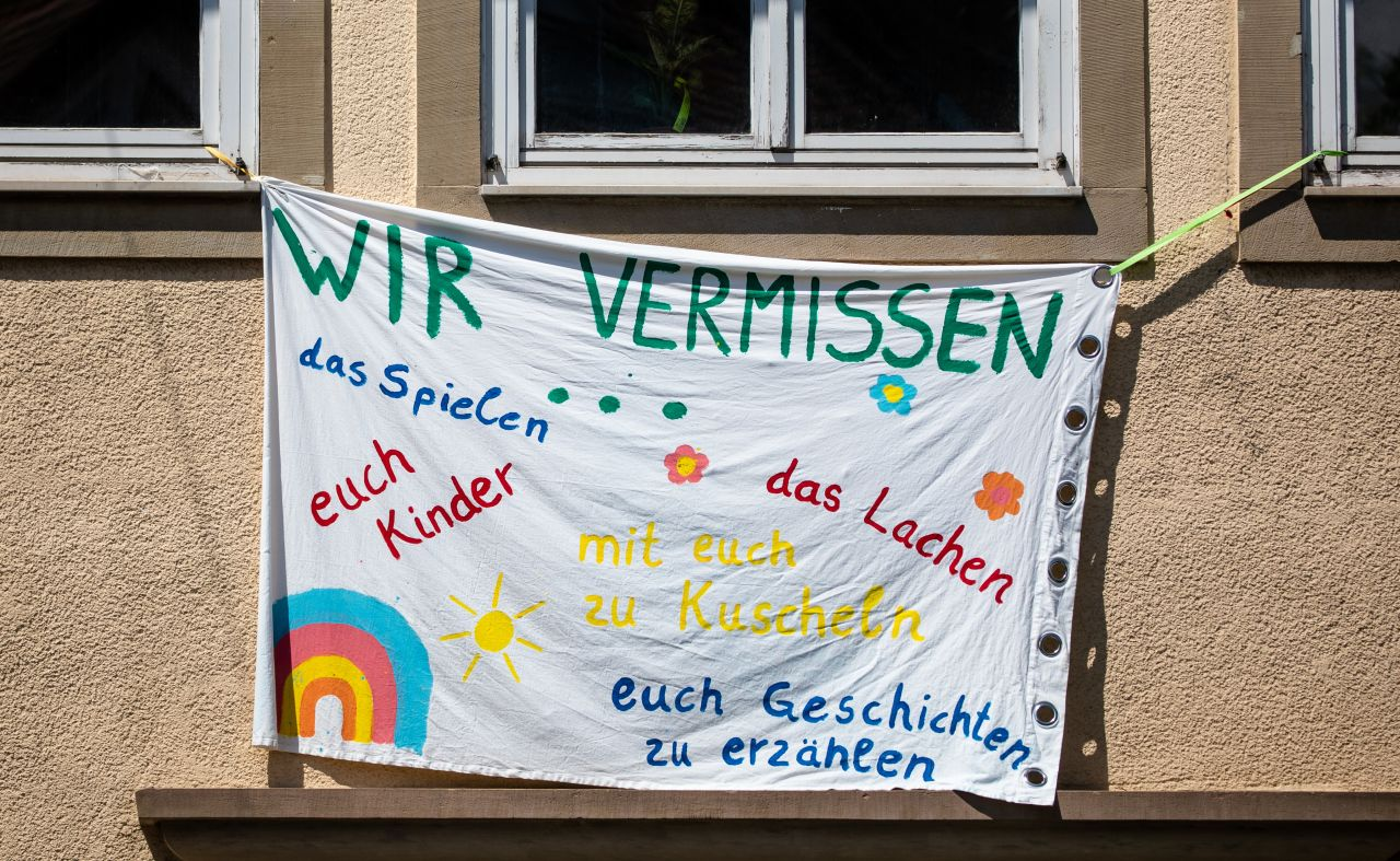 """""""Wir vermissen das Spielen, das Lachen, euch Kinder, mit euch Kuscheln und mit euch Geschichten erzählen"""" steht auf einem großen Banner an der Fassade eines Kindergartens in Baden-Württemberg."""