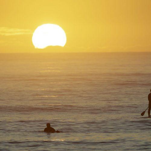Surfer in Neuseeland genießen den Sonnenuntergang am Strand, nachdem die Beschränkungen wegen des Corona-Virus ausgehoben wurden.